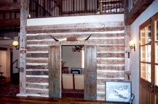 Logs from an original hand hewn log cabin were used to form a den on the ground level.